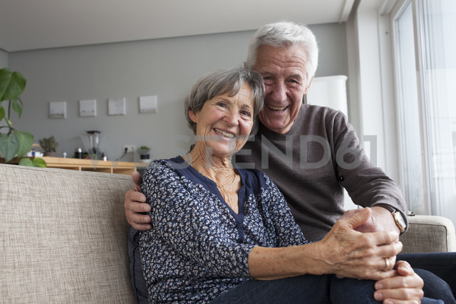 Happy senior couple sitting on the couch in the living room holding hands - RBF004132