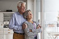 Portrait of confident senior couple looking through window at home - RBF004147
