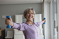 Portrait of happy senior woman doing fitness exercise with dumbbells at home - RBF004153