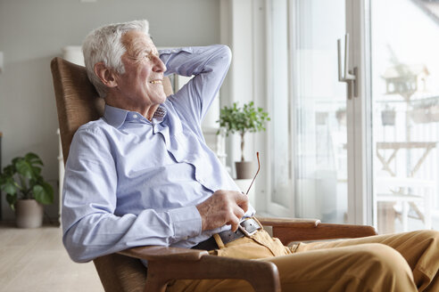 Portrait of senior man relaxing on armchair at home - RBF004156