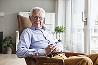 Portrait of smiling senior man sitting on armchair at home - RBF004159