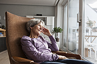 Portrait of senior woman sitting on armchair at home looking through window - RBF004168