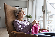 Portrait of senior woman sitting on armchair at home knitting - RBF004171