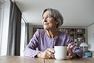 Portrait of senior woman sitting at table with cup of coffee looking through window - RBF004174