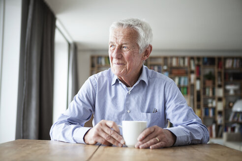 Portrait of pensive senior man sitting at table with cup of coffee looking through window - RBF004177