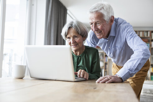 Senior couple using laptop at home - RBF004180