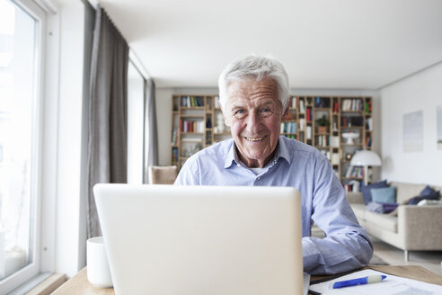 Portrait of senior man sitting at table in the living room with laptop - RBF004183