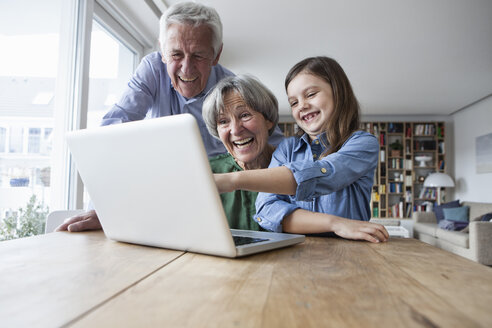 Grandparents and their granddaughter having fun with laptop at home - RBF004189