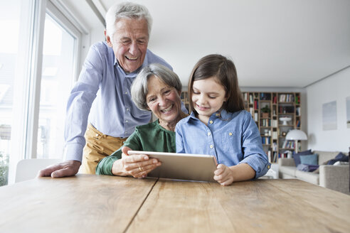Grandparents and their granddaughter using digital tablet at home - RBF004192