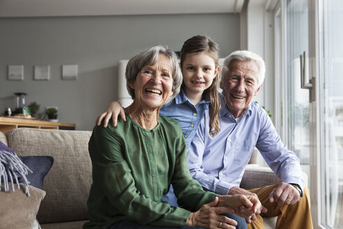 Family portrait of grandparents and their granddaughter at home - RBF004201