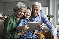 Grandparents and their granddaughter sitting together on the couch looking at digital tablet - RBF004204