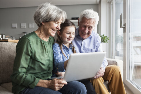 Grandparents and their granddaughter sitting together on the couch looking at digital tablet - RBF004207