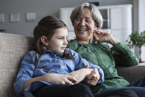 Grandmother and her granddaughter sitting together on the couch at home - RBF004213