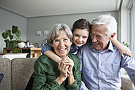 Family portrait of grandparents and their granddaughter at home - RBF004219
