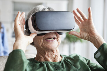Senior woman using Virtual Reality Glasses at home - RBF004222