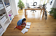 Woman sitting on the floor reading documents - FKF001693