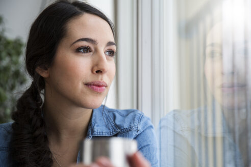 Woman holding cup of coffee looking out of window - FKF001705