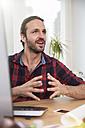 Man at desk in office talking - FKF001714