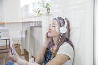 Young woman sitting behind windowpane listening music with headphones - FMKF002503