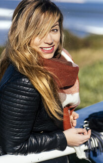 Portrait of smiling young woman outdoors - MGOF001479