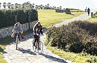 Two young women riding bicycle along a path - MGOF001482