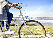 Woman riding bicycle at the coast - MGOF001488