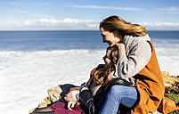 Spain, Gijon, two young women having fun near the sea - MGOF001494