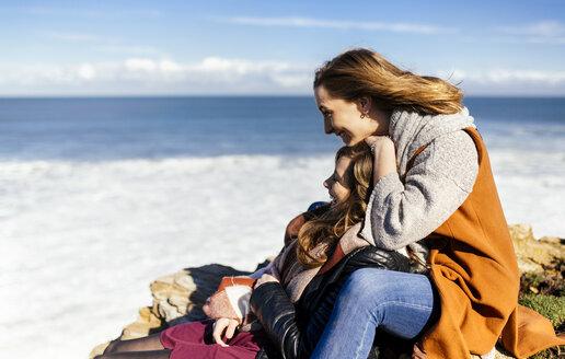 Spain, Gijon, two young women having fun near the sea - MGOF001494