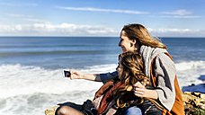 Spain, Gijon, two young women having fun with a smartphone near the sea - MGOF001497
