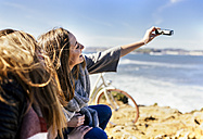 Spain, Gijon, two young women taking a selfie near the sea - MGOF001500