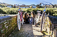 Two young women with bicycles eating apples outside - MGOF001512