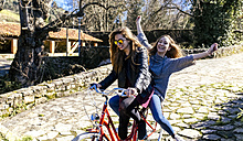 Two playful young women riding bicycle - MGOF001518