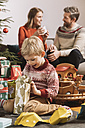 Little boy happily looking at Christmas gift with parents in background - MFF002756