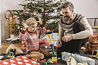 Father and son playing with building bricks in front of Christmas tree - MFF002762