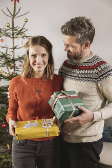 Couple with Christmas gifts standing in front of tree - MFF002780