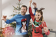 Two people with ugly Christmas sweaters dancing in front of tree - MFF002783
