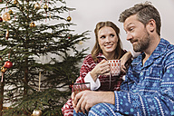 Tired couple in Christmas pyjamas - MFF002789