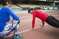 Athletes training for race in stadium - KIJF000214