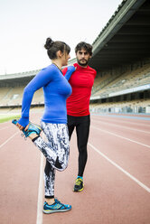 Athletes training for race in stadium - KIJF000220