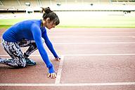 Female athlete training for race in stadium - KIJF000223