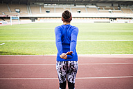 Female athlete training in stadium, stretching arms, rear view - KIJF000226