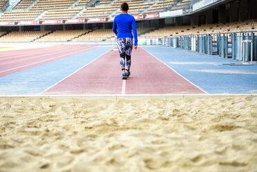 Female athlete training for long jump in stadium - KIJF000229