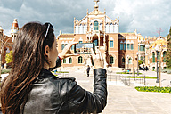 Spain, Barcelona, woman taking pictures of Sant Pau Art Nouveau Site with her smartphone - GEMF000783