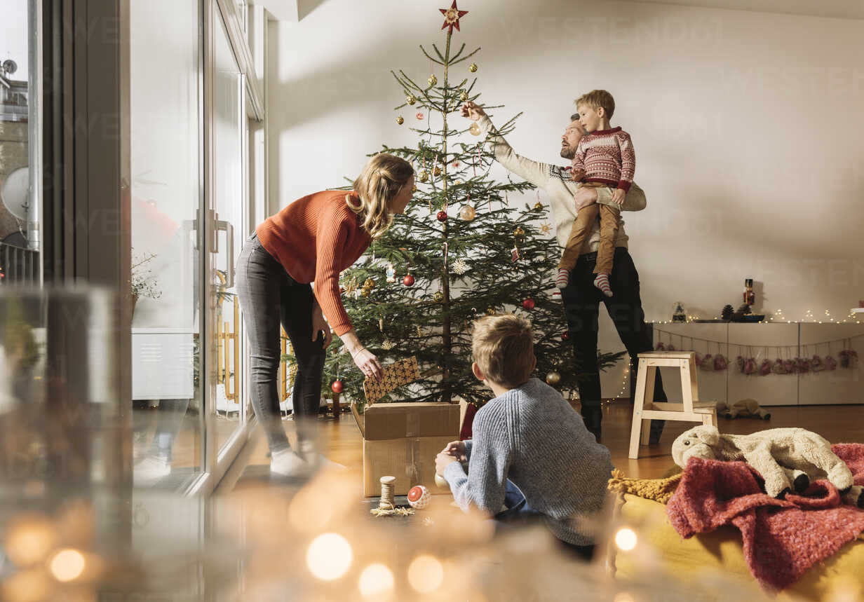 Family decorating Christmas tree - MFF002797 - Mareen Fischinger/Westend61