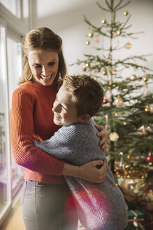 Happy mother and son hugging by Christmas tree - MFF002815