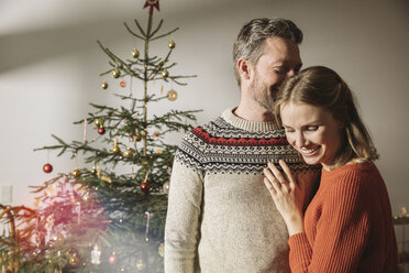 Happy couple standing in front of Christmas tree - MFF002818