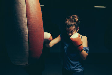Female boxer exercising at punch bag - ZEDF000076