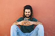 Portrait of smiling young man with dreadlocks and beard looking at his smartphone in front of a reddish wall - KIJF000234