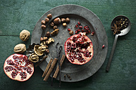 Two halves of pomegranate, different spices and nuts on tin plate - ASF005861