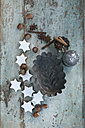 Cake pans, cinnamon stars, cinnamon sticks, hazelnuts and star anise on wood - ASF005864